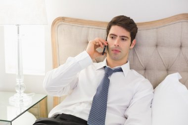 Smiling well dressed man using mobile phone in bed