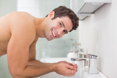 Portrait of shirtless man washing face in bathroom