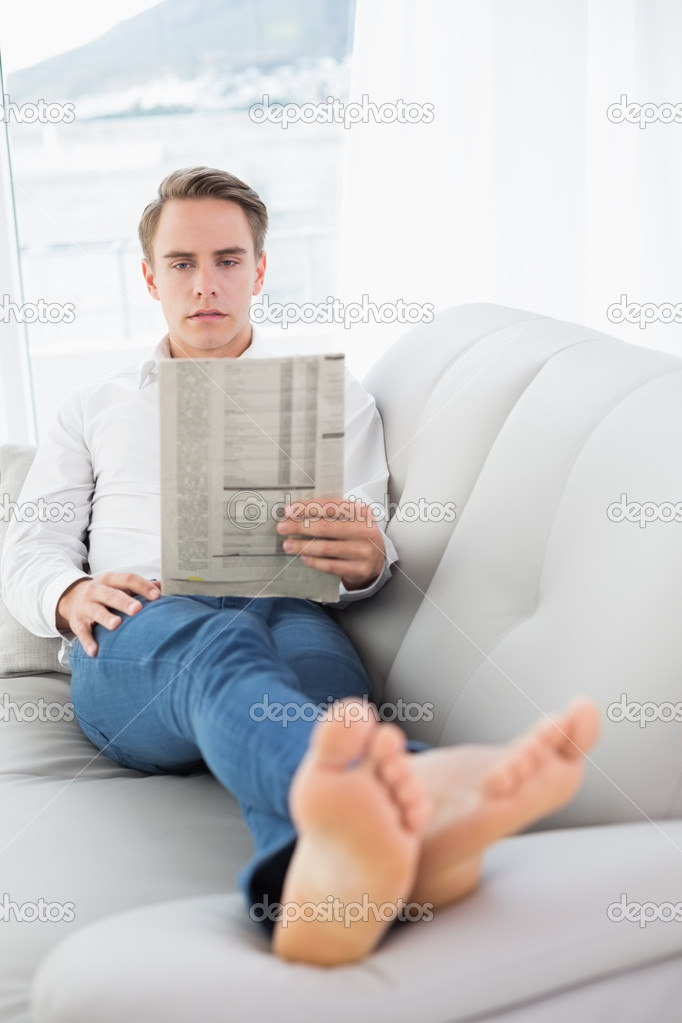 Full length of a relaxed man reading newspaper on sofa ...