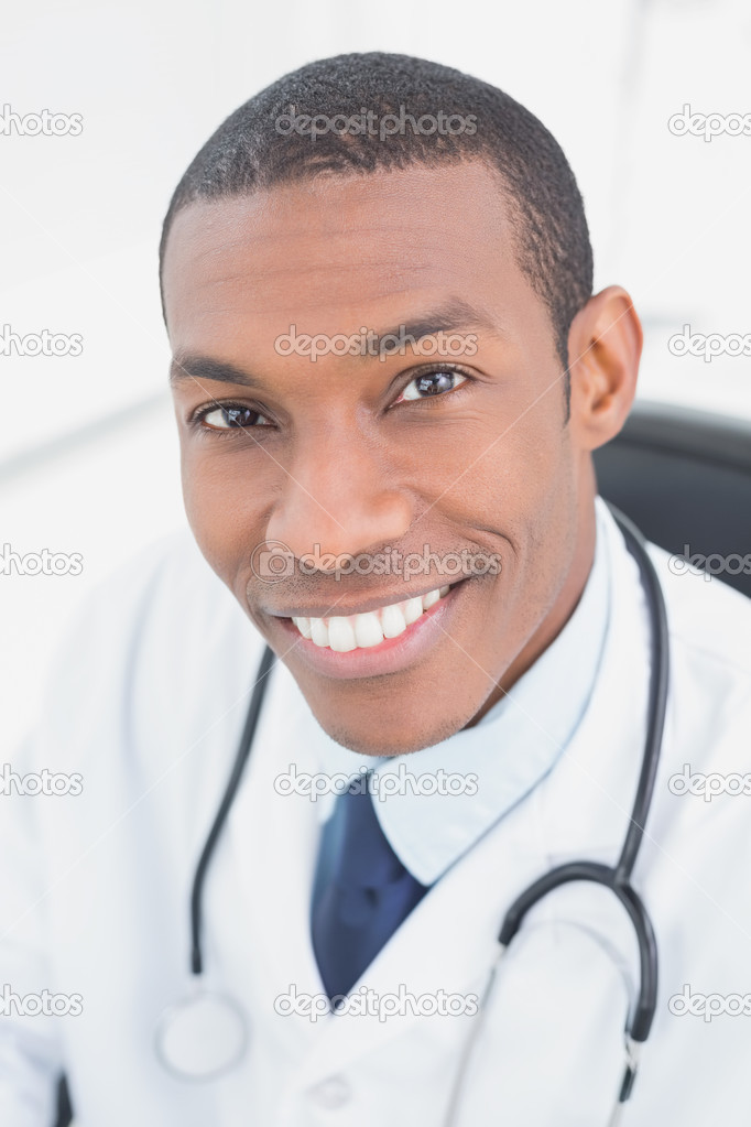 Close up portrait of a smiling male doctor in medical office