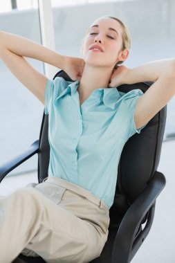 Tired chic businesswoman relaxing sitting on her swivel chair