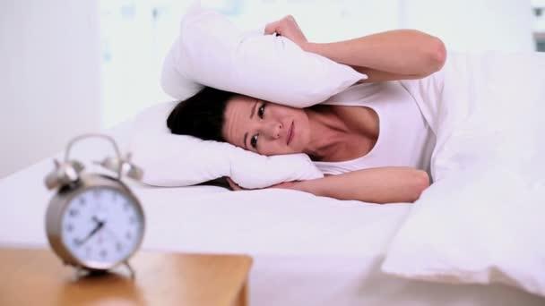 vyčerpaná žena ležící na posteli, pokrývající její uši