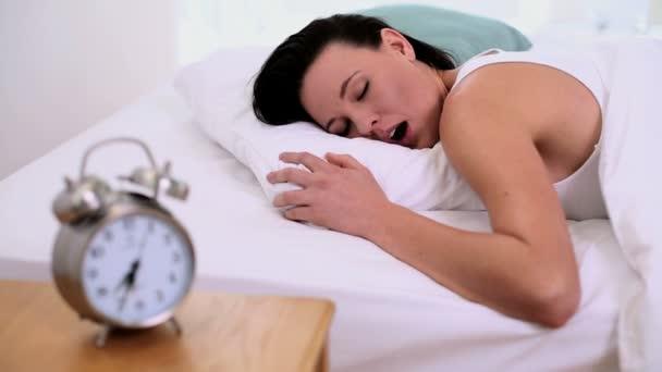roztomilá mladá žena podřimuje, ležící v posteli