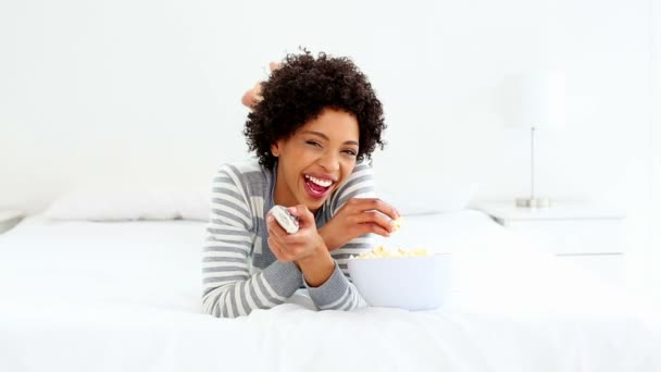 Cute laughing woman lying on bed watching tv