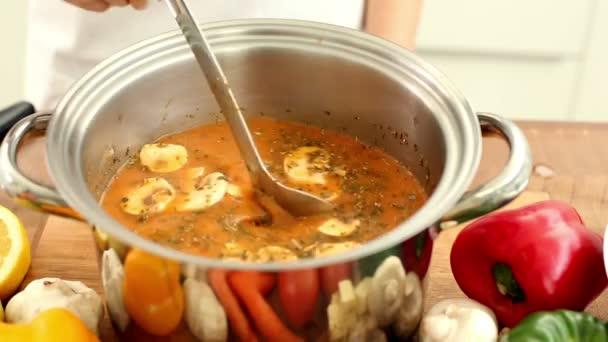 žena v pánvi za stálého míchání polévku