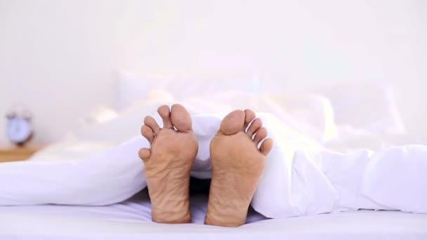 Mann wackelt mit den Zehen unter der Bettdecke