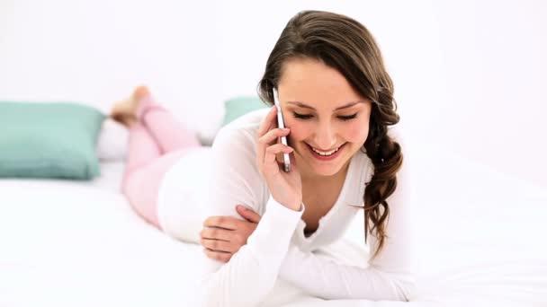 usmívající se žena leží na posteli, chatování na telefonu