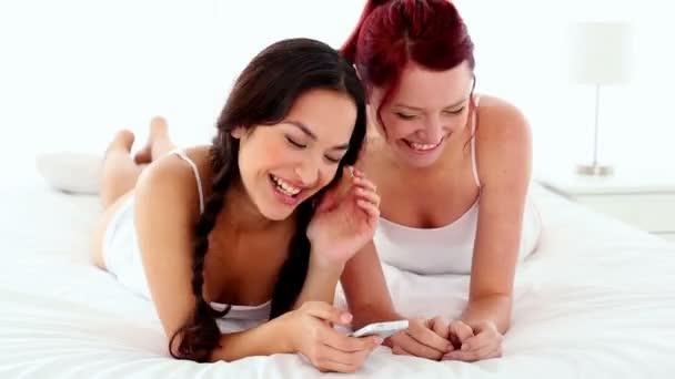 vidám nevetés nők gazdaság egy smartphone ágyon