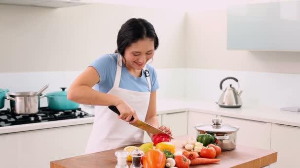 usmívající se žena krájení zeleniny s velkým nožem