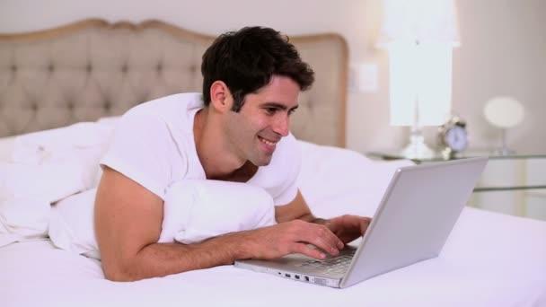 usměvavý pohledný muž pomocí notebooku v posteli