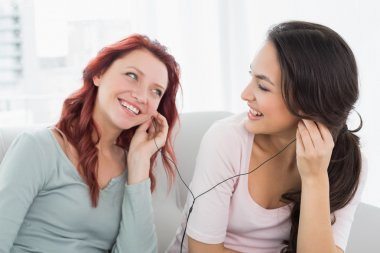 Friends listening music through earphones together at home