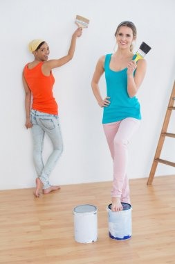 Full length of two female friends with paint brushes and cans in a new house stock vector