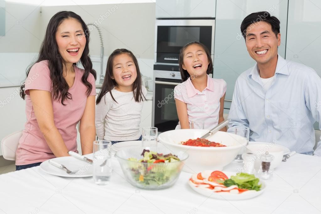 Retrato de una familia sonriente sentada en mesa de for Cocina en familia
