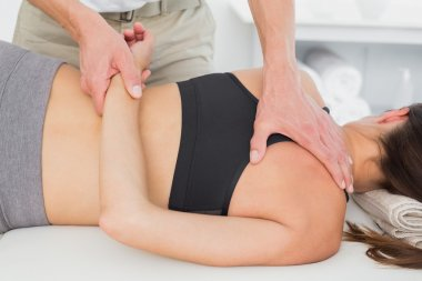 Male physiotherapist massaging woman's body