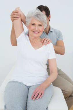 Physiotherapist stretching a smiling senior woman's arm