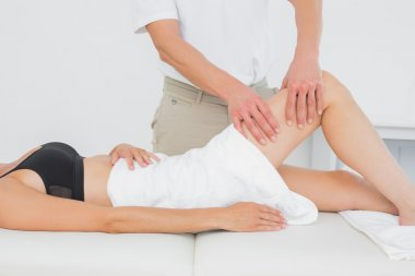 Physiotherapist examining a young woman's leg