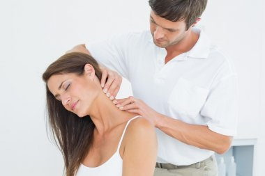 Male chiropractor massaging a young woman's neck