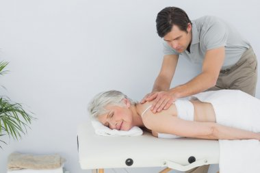 Male physiotherapist massaging a senior woman's back
