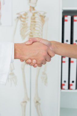 Extreme close-up of a doctor and patient shaking hands