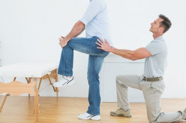Side view of a physiotherapist examining man's back