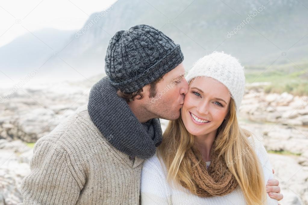 Man kissing a woman on rocky landscape
