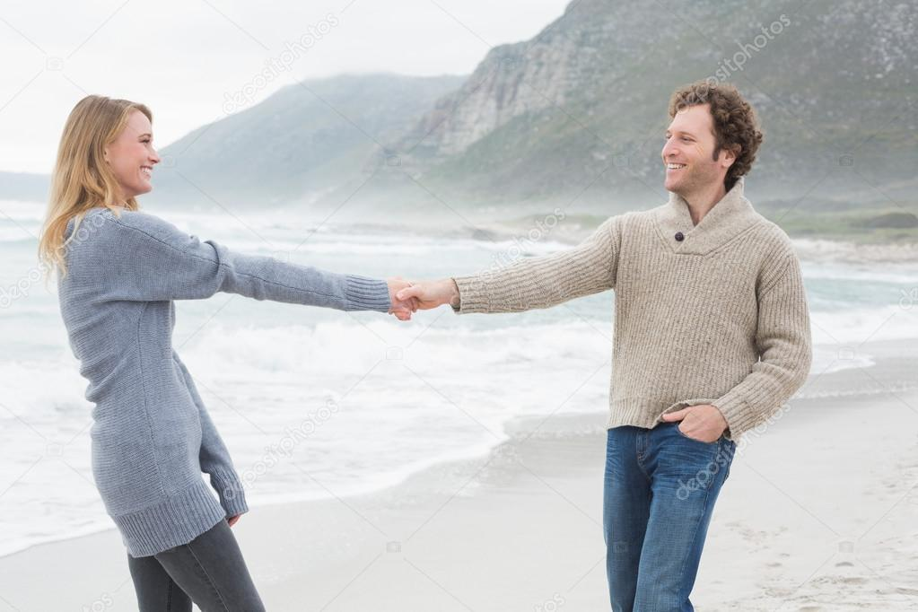 Happy couple holding hands at beach