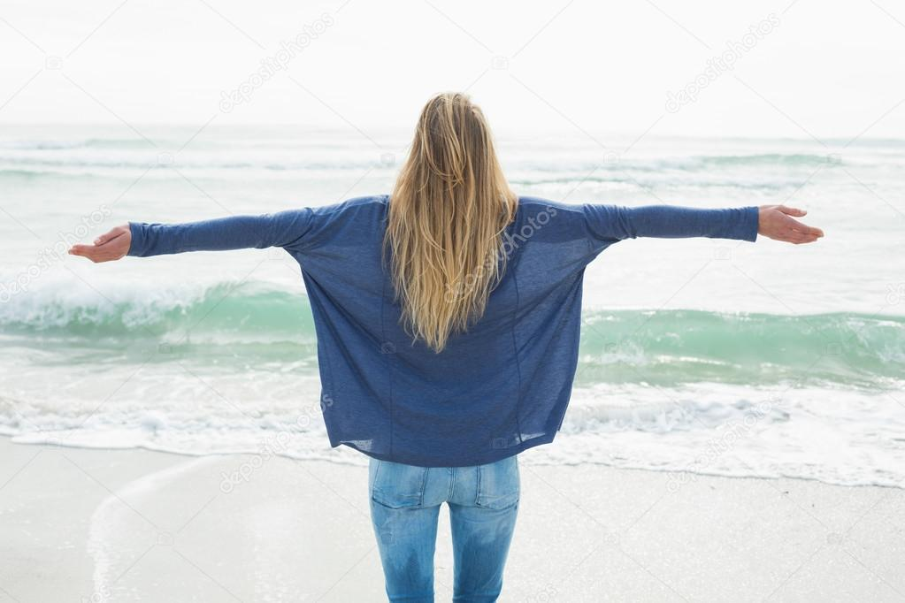 Rear view of a blond with arms outstretched at beach