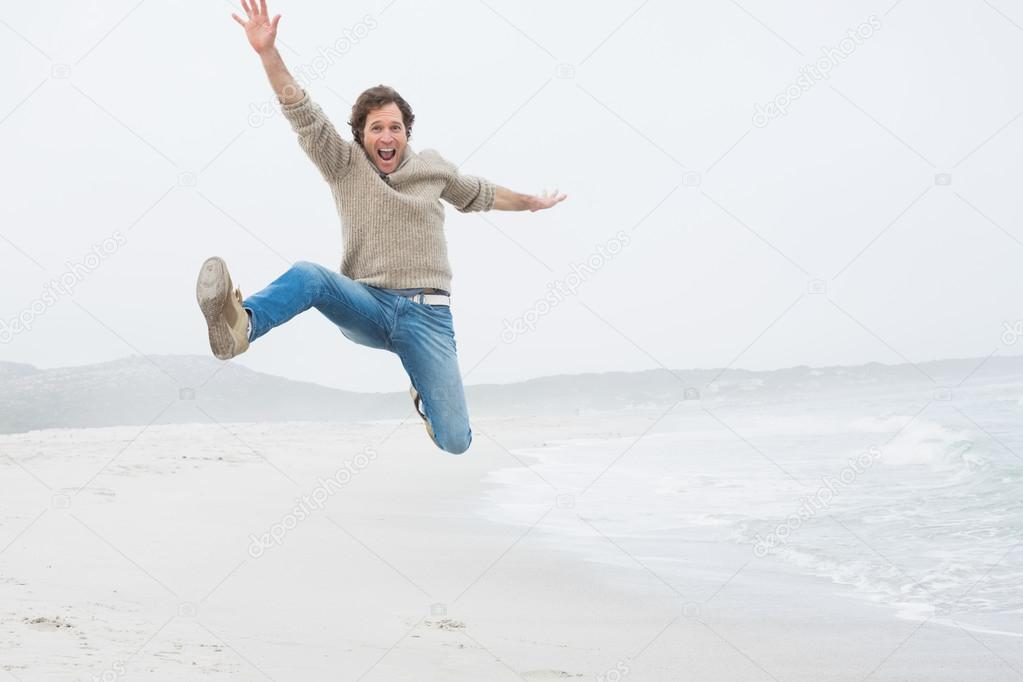 Casual young man jumping at beach