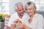 Fotografie Happy mature couple with a flower in living room