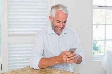 Smiling relaxed mature man text messaging at home stock vector