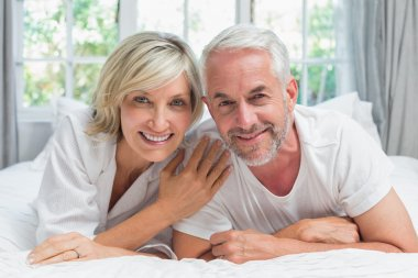 Happy mature couple lying in bed