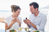 Man surprising woman with a wedding ring at lunch table