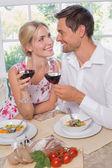 milující pár s poháry na sebe při pohledu na jídlo
