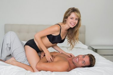 Cheerful romantic couple in underwear in bed