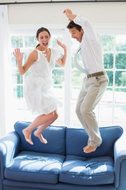 Cheerful young couple jumping on couch