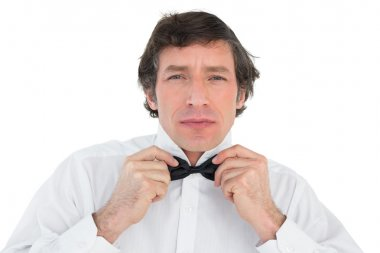 Handsome groom corrects bow tie