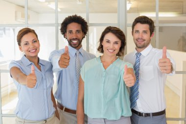 Portrait of young business colleagues gesturing thumbs up in the office stock vector