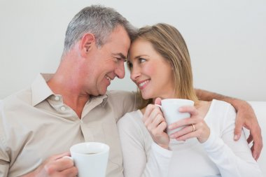 Loving couple with coffee cups in living room