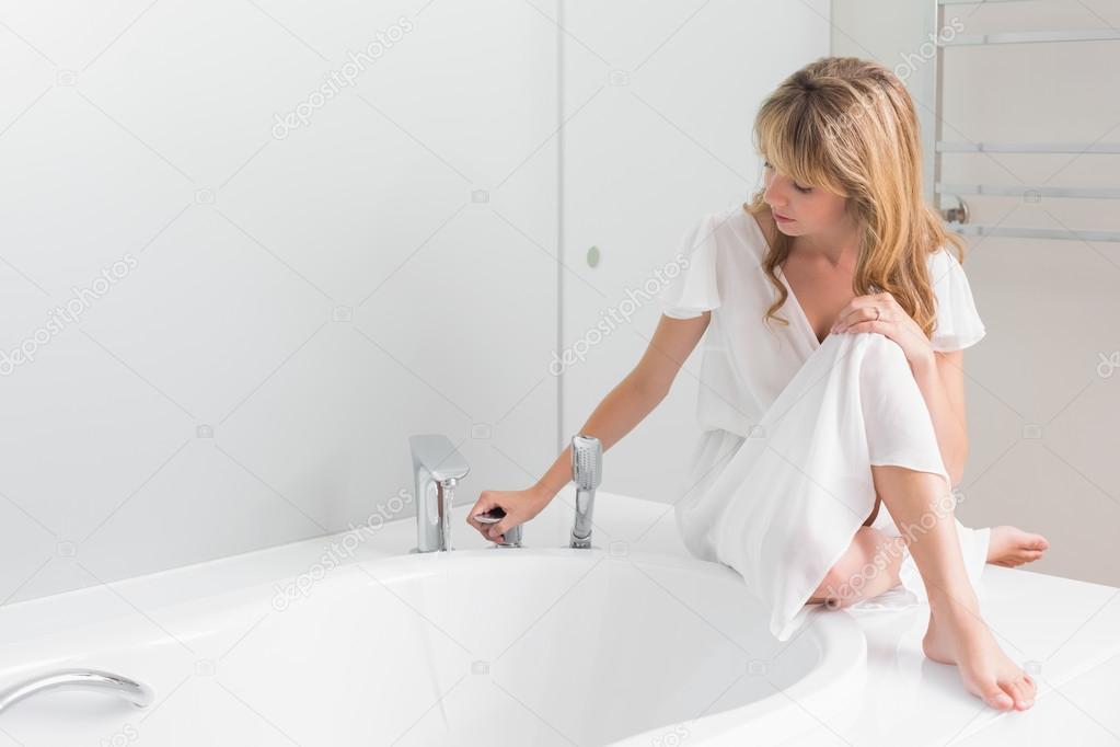 Vasca Da Bagno Seduta : Bellissima giovane donna seduta sul bordo della vasca da bagno