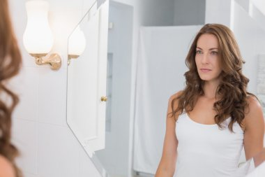 Woman looking at herself in the bathroom mirror