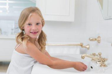 Portrait of a cute girl washing hands at washbasin