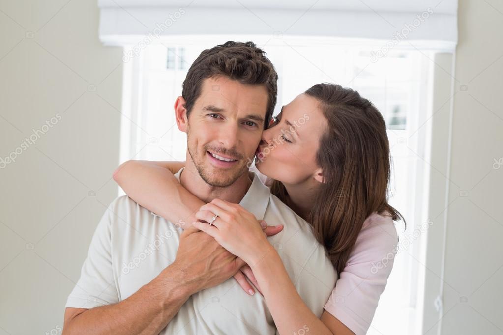 Frau umarmt und küsst Mann von hinten - Stockfotografie