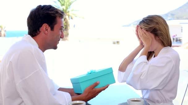 pohledný muž překvapující svou přítelkyni s dárkem