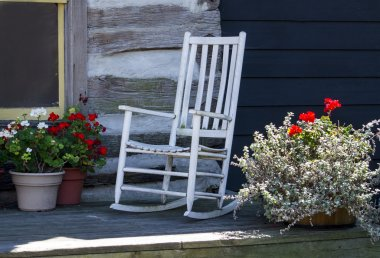 White rocker on front porch of a log cabin
