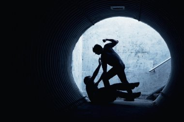 Young man being mugged in a dark tunnel