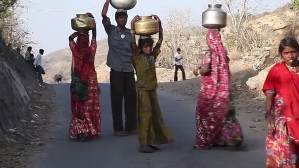 Indian village girls carry jugs of water