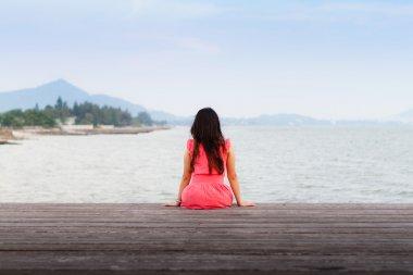 Sad woman sitting alone on a jetty.