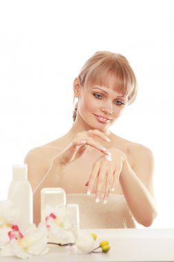 Beautiful woman putting cream on her hand