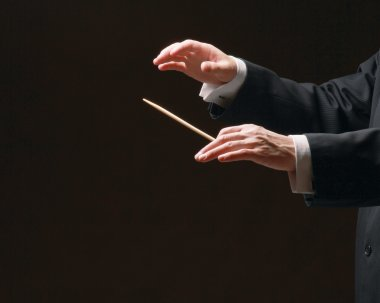 Concert conductor's hands with a baton