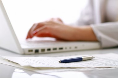 Close-up of businesswoman typing documents on keyboard